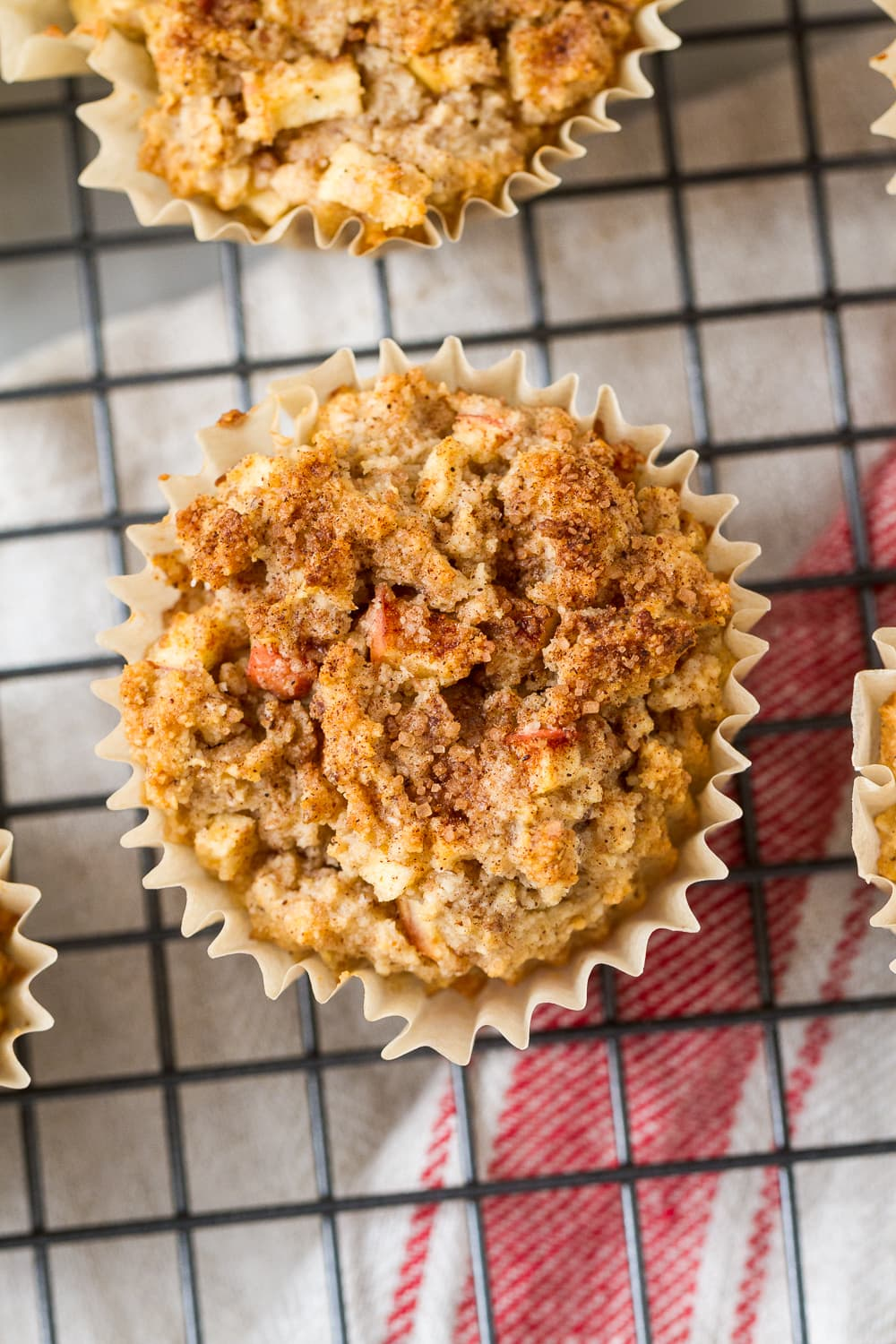 top down, close up view of apple cinnamon muffin with cinnamon sugar topping cooling on a wire rack