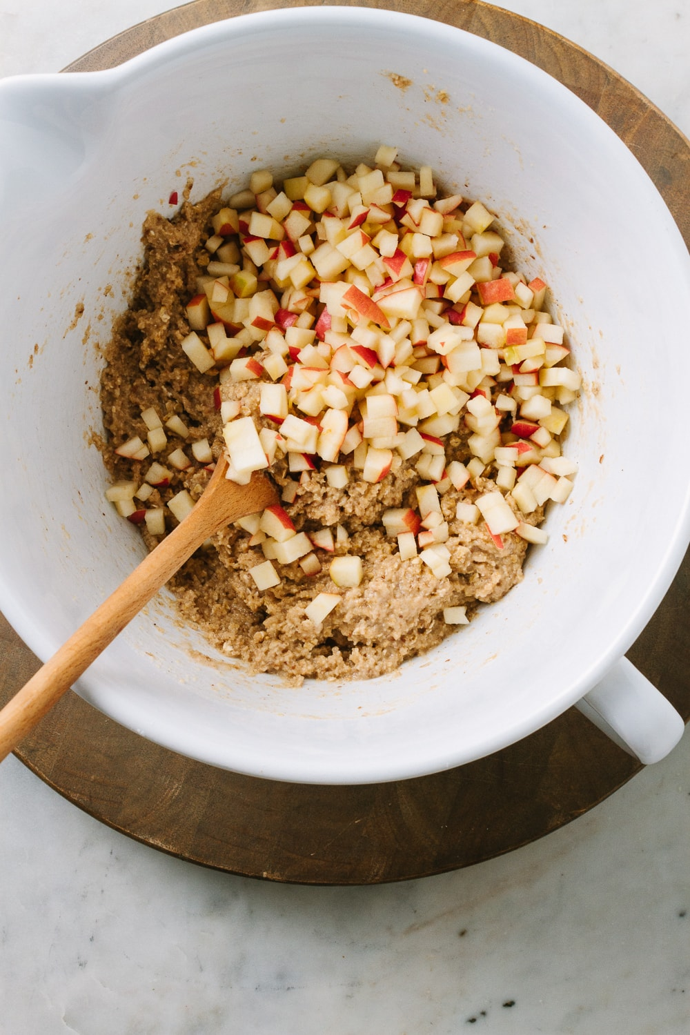 top down view of white mixing bowl with apple cinnamon muffin batter mixed and finely diced apples added before mixing, on a round wooden cutting board