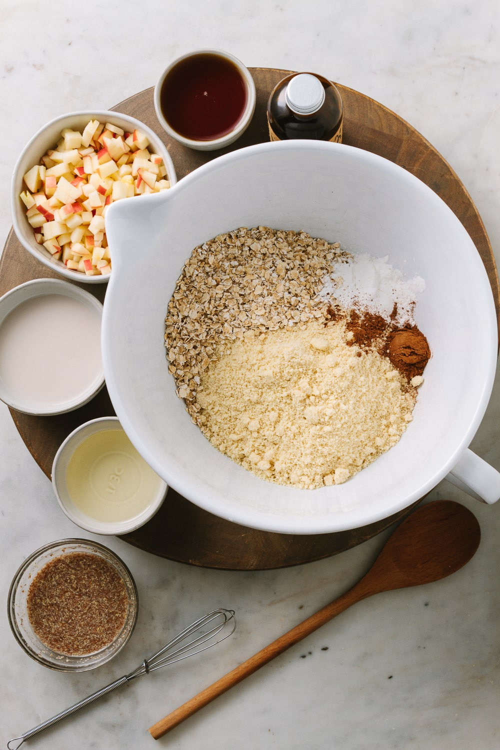 top down view of a mixing bowl filled with almond flour, oats, baking powder, salt and cinnamon, surrounded by small bowls filled with finely diced apples, plant milk, pure maple syrup, oil, flax egg, and bottle of vanilla on a circular brown wooden cutting board