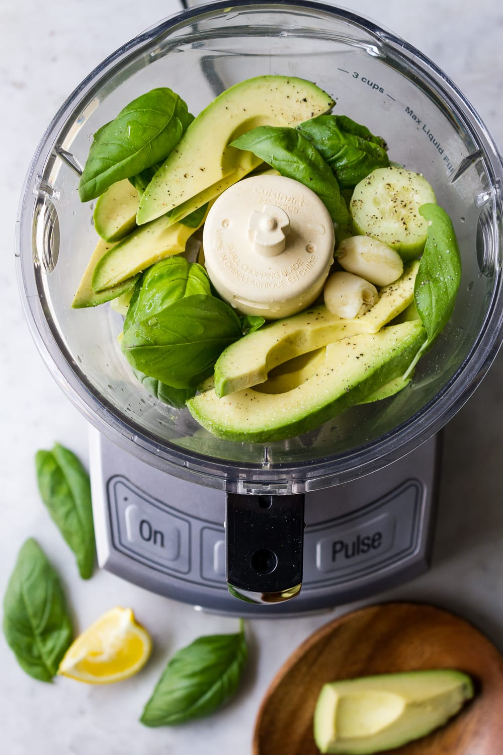 top down view of food processor with sliced avocado, cucumbers, basil leaves, salt, garlic, pepper and lemon juice before putting the lid on to process into a creamy sauce