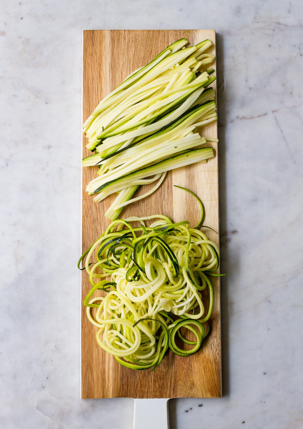 top down view of julienned zucchin and spiralized zuccini on a long rectangular wooden serving paddle board with white handle, on a marble slab
