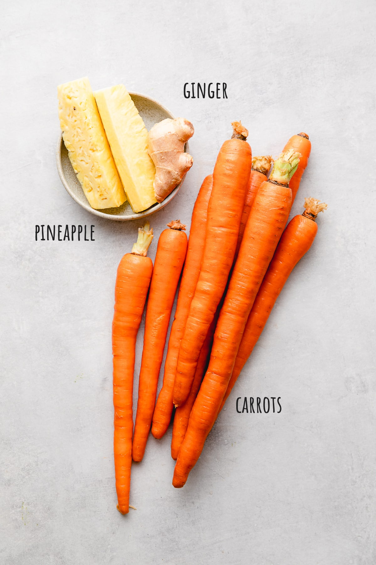 top down view of ingredients used to make carrot juice with pineapple and giner.