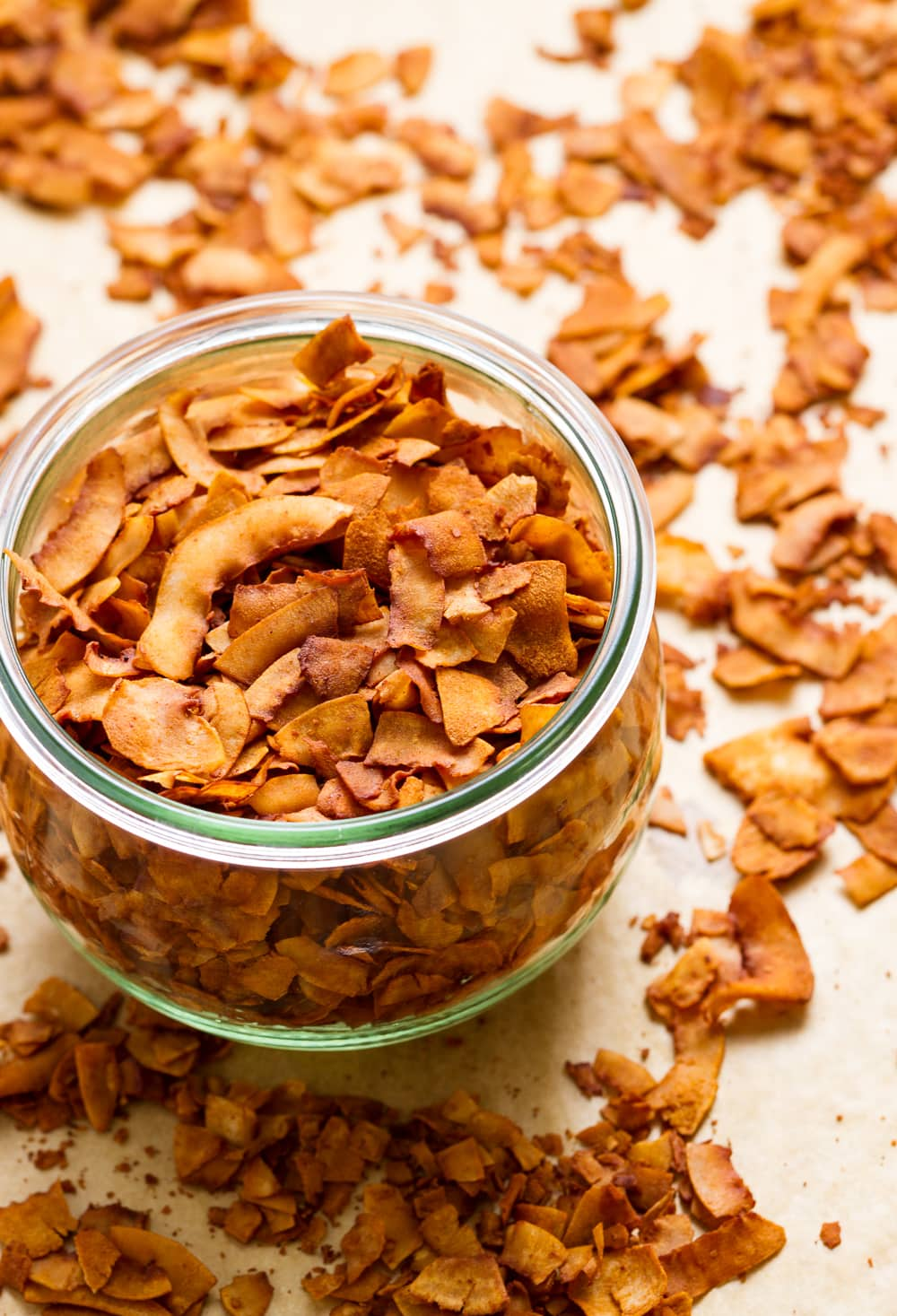 side angle view of freshly made coconut bacon in a glass mason jar.