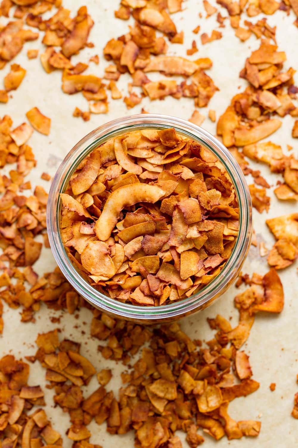 top down view of freshly made coconut bacon in a glass mason jar.