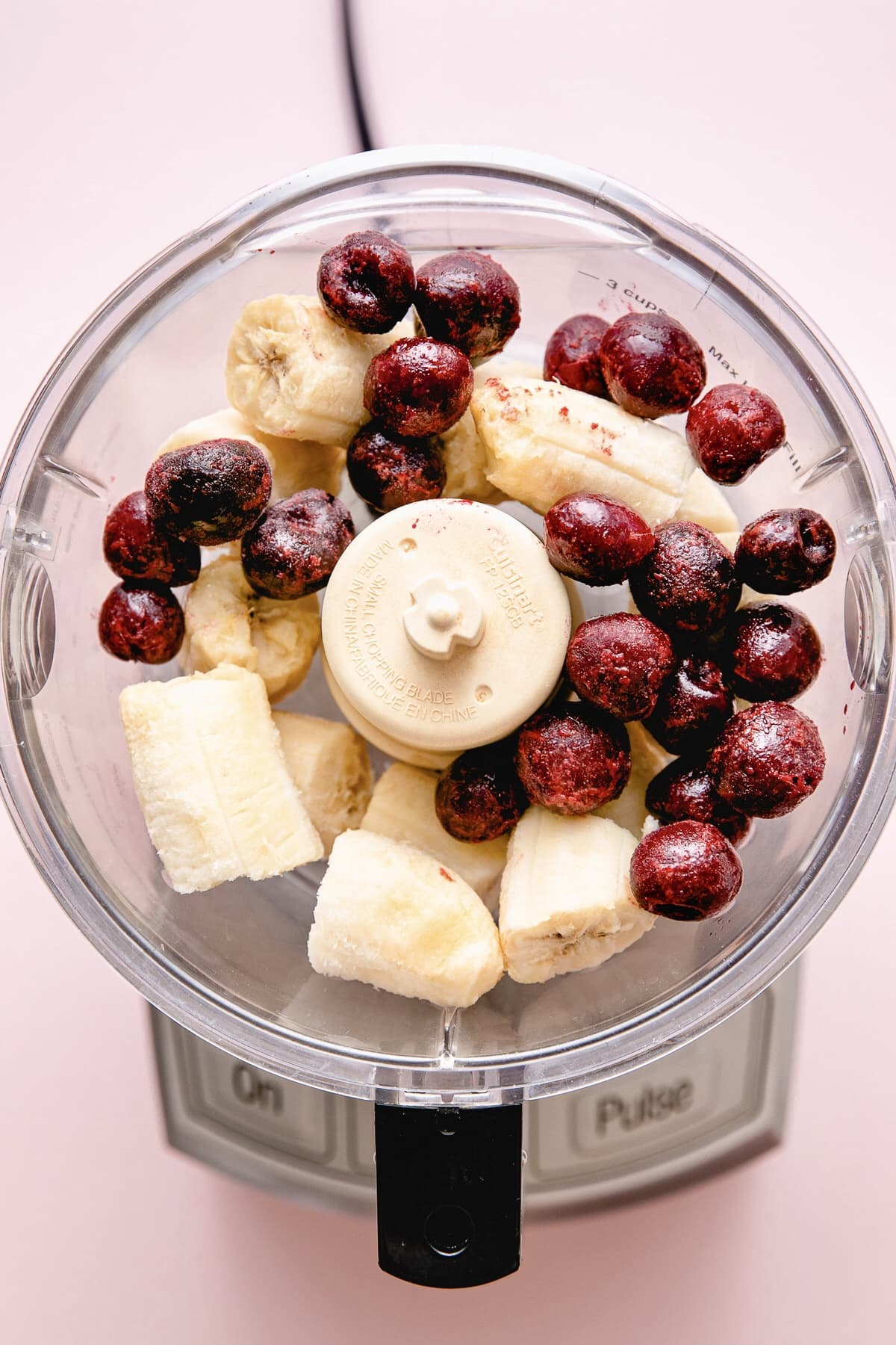 top down view of banana and cherries added to food processor.