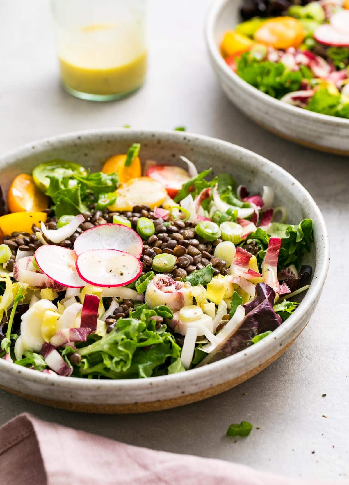 side angle view of french lentil and bitter greens salad in a bowl.