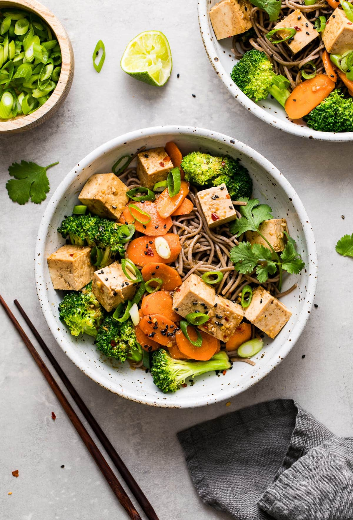 top down view of bowl with sesame soba noodle salad with tofu and items surrounding.