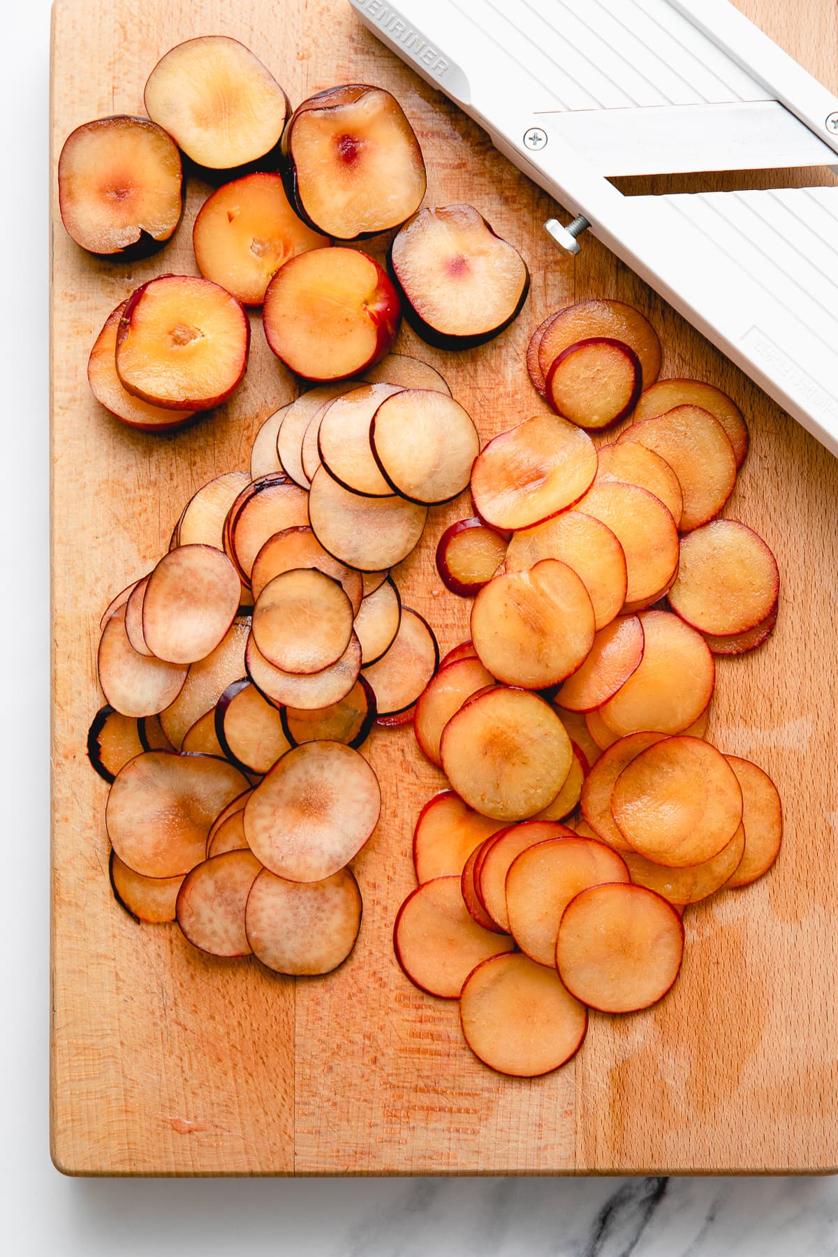 top down view of sliced plums on wooden cutting board.