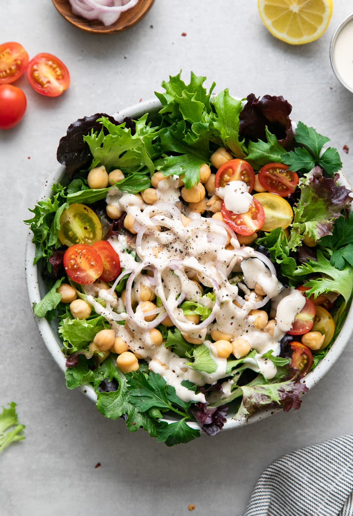 top down view of leafy green salad with chickpeas and dressed with lemony tahini dressing.