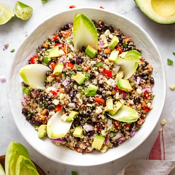 top down view of quinoa cowboy caviar in a large serving bowl with whole endive leaves for scooping.