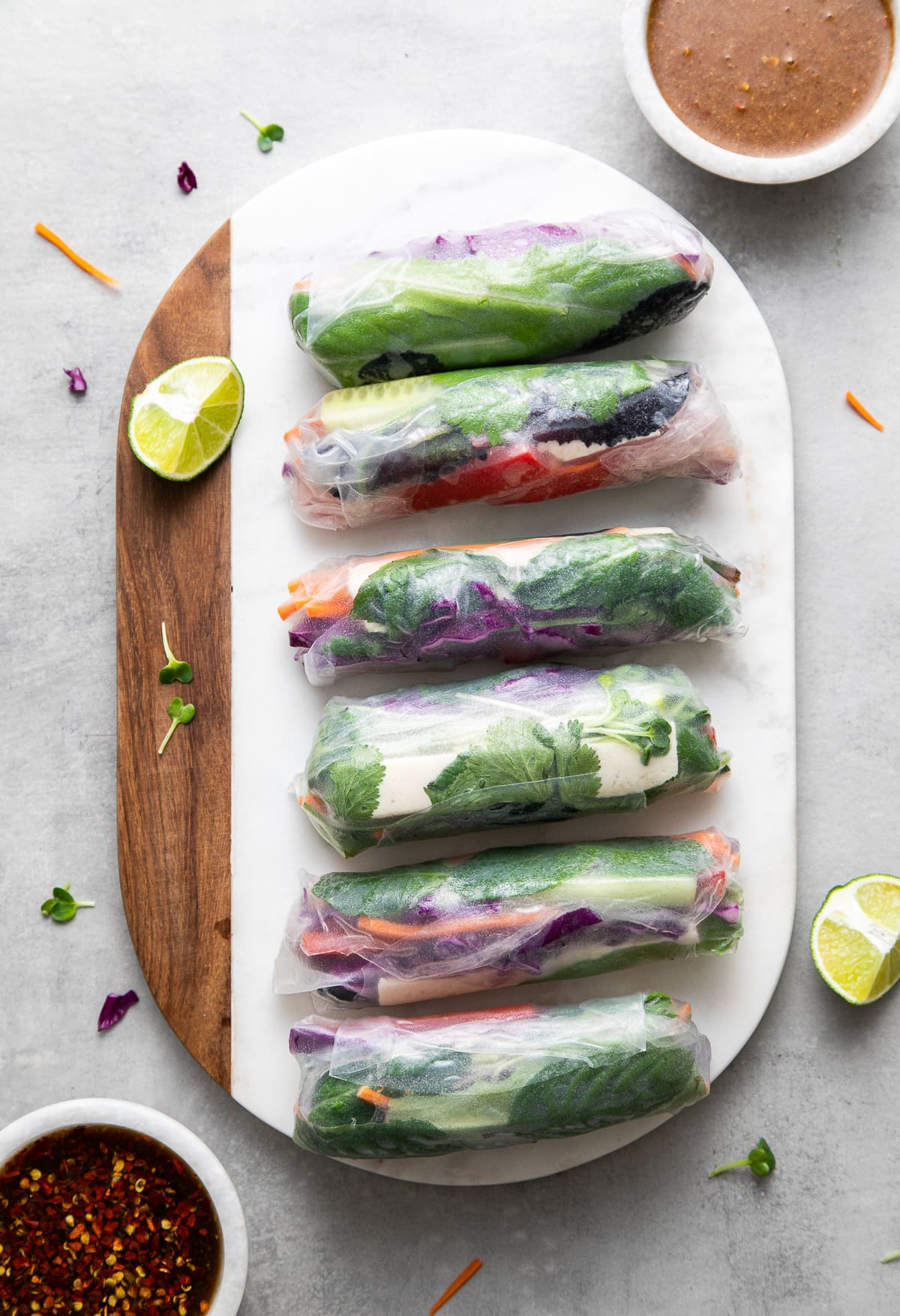 top down view of summer rolls on a marble serving board with dipping sauces.
