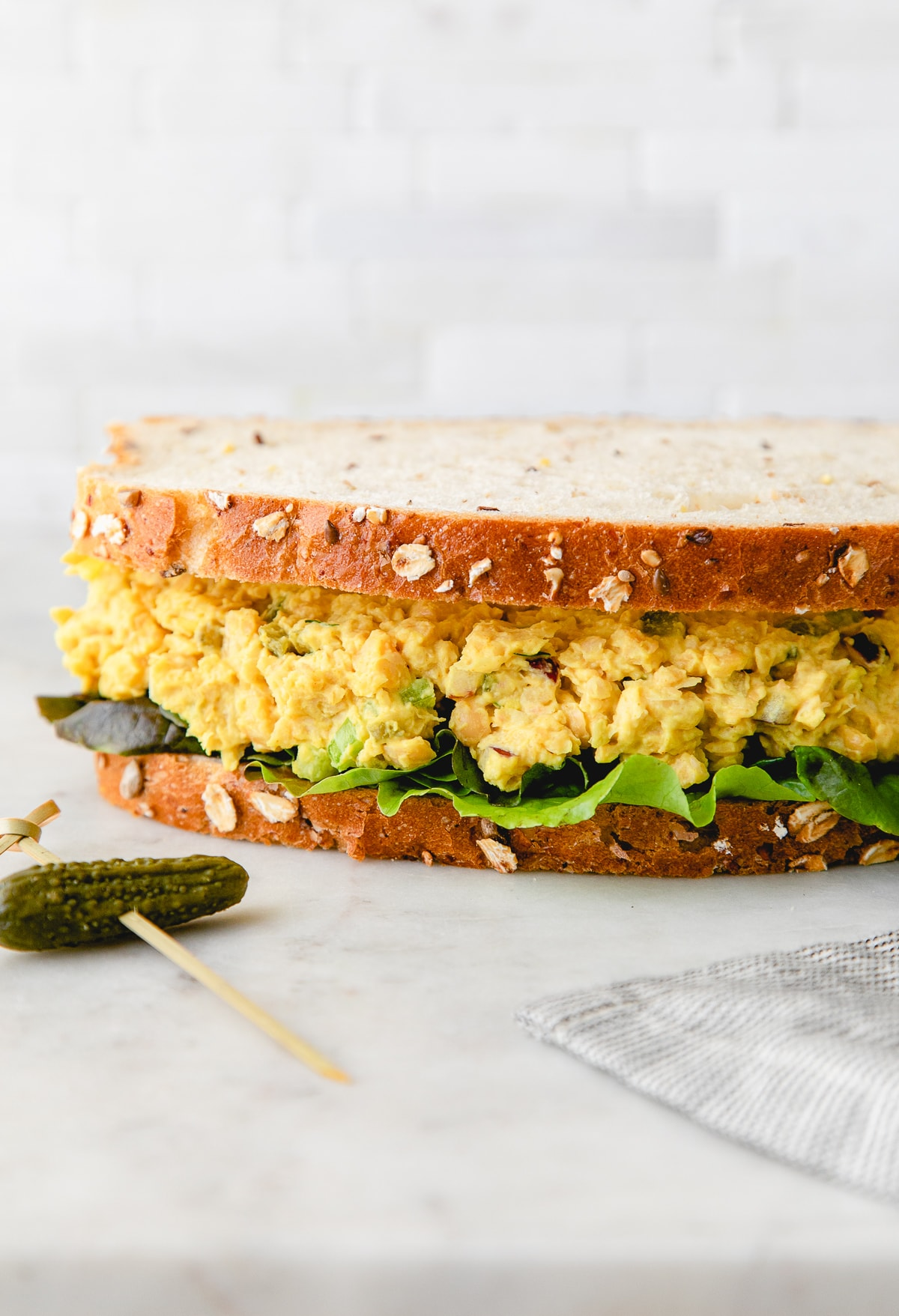 head on view of chickpea egg salad sandwich with items surrounding.