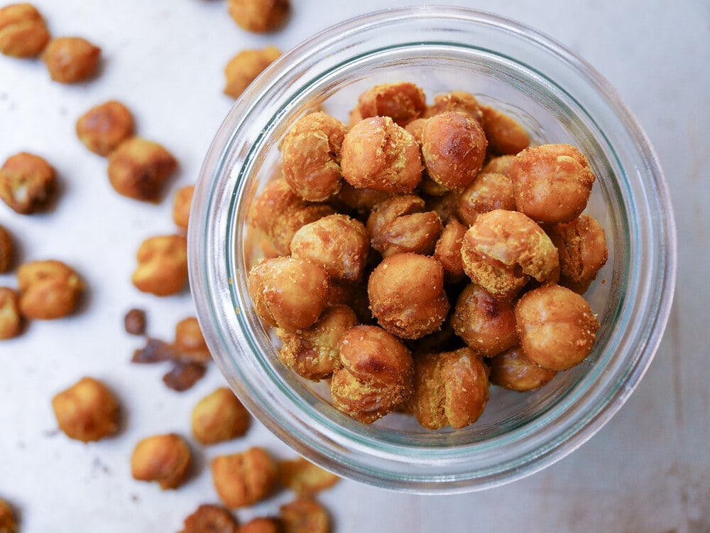 top down view of a glass jar filled with curry sriracha roasted chickpeas.