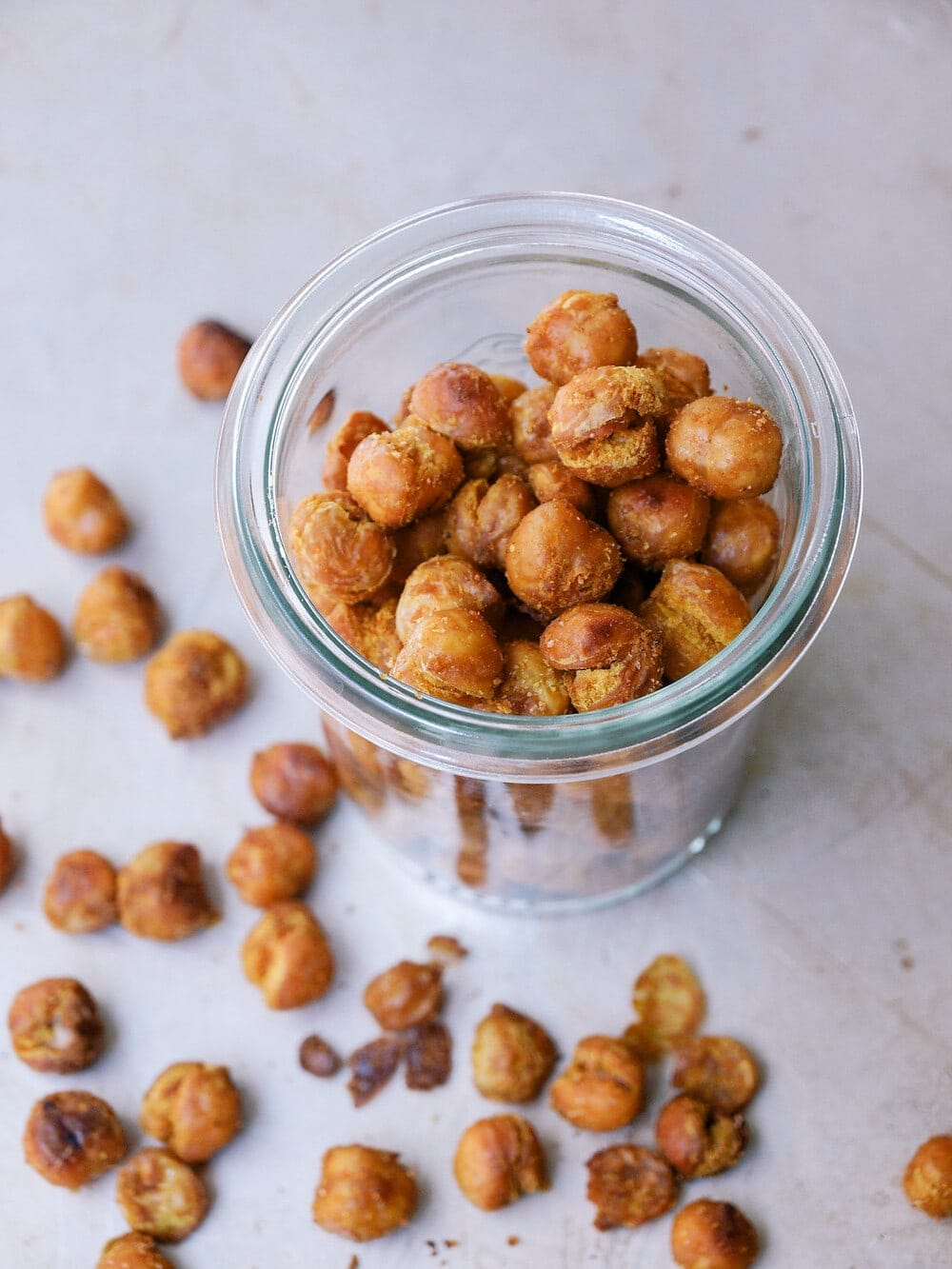 top down side angle view of a glass jar filled with curry sriracha roasted chickpeas.