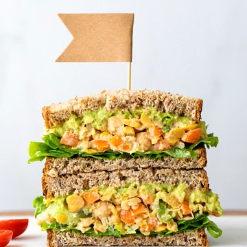 head on view of the best mashed chickpea salad sandwich cut in half and stacked.