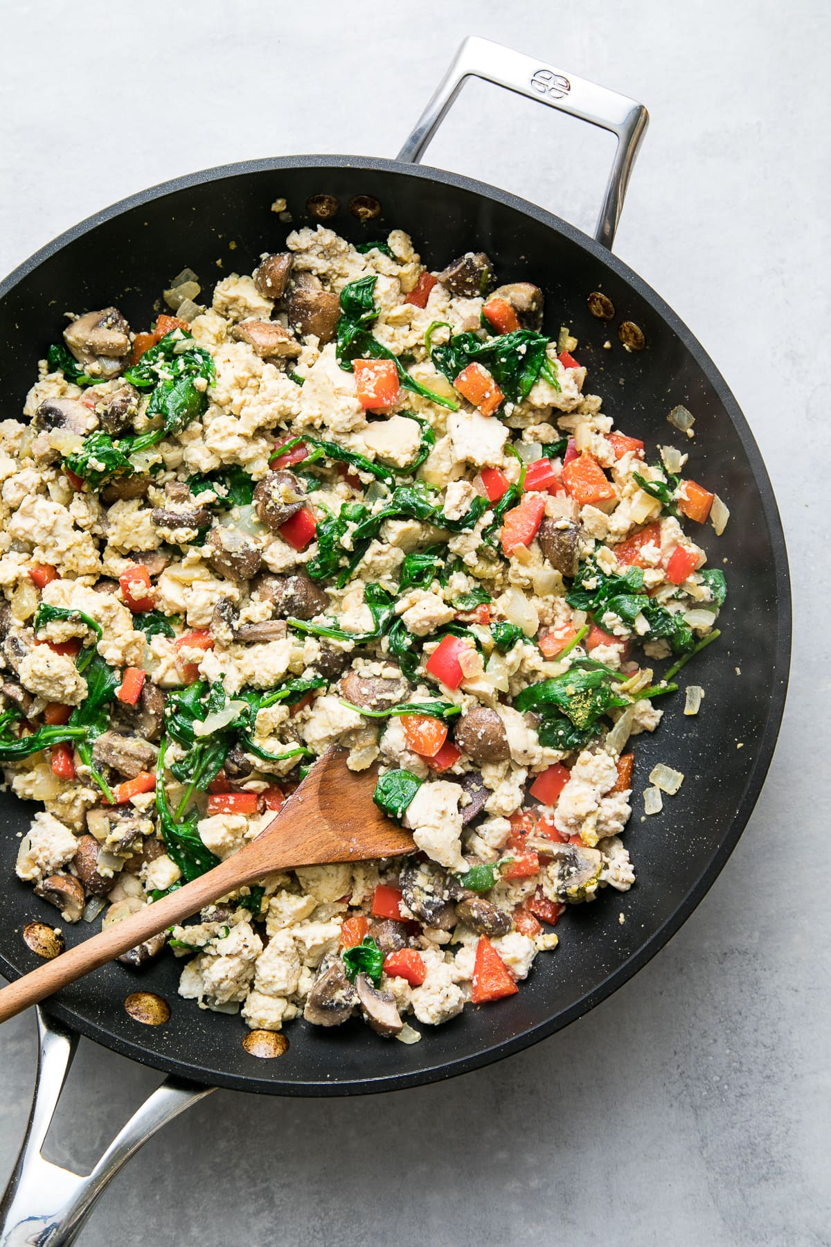 top down view of veggie filled tofu scramble in a skillet with wooden spoon.