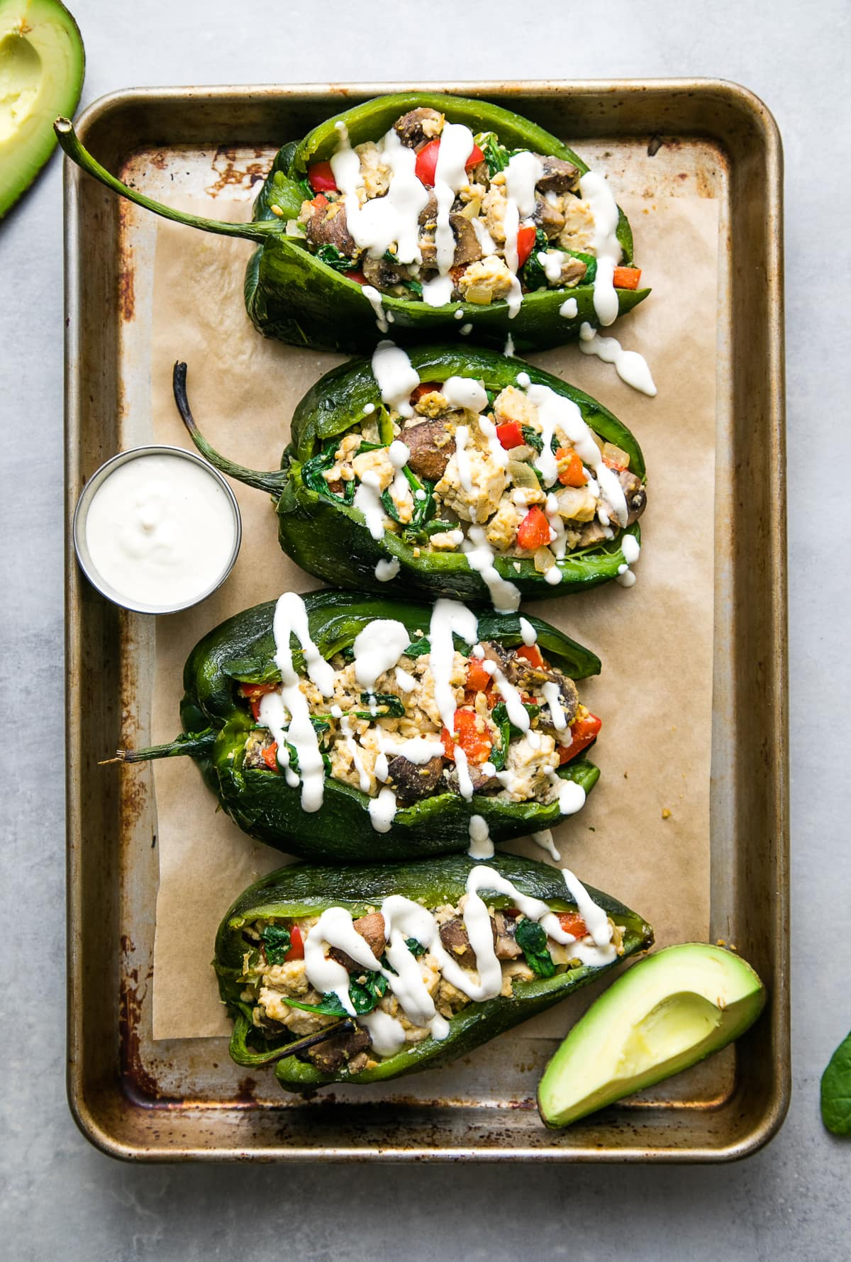 top down view of stuffed poblano peppers with tofu scramble and drizzled with cashew cream on a baking sheet.