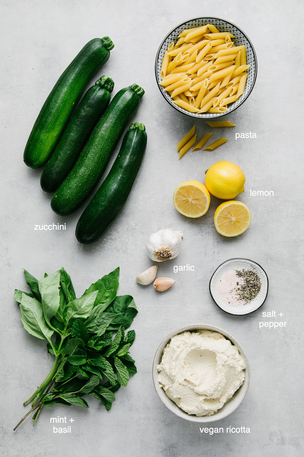 top down view of ingredients used to make vegan zucchini ricotta pasta with basil and mint.