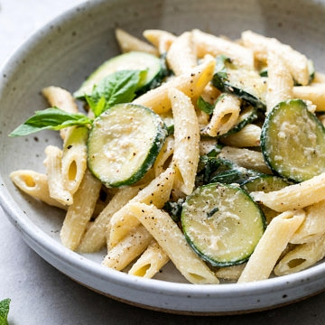 side angle view of healthy, vegan zucchini ricotta pasta with basil and mint in a bowl with items surrounding.