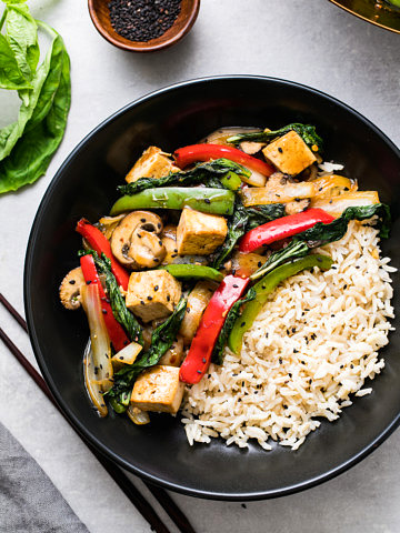 top down view of a serving of thai basil stir fry with tofu and veggies, and rice on the side, in a black bowl.