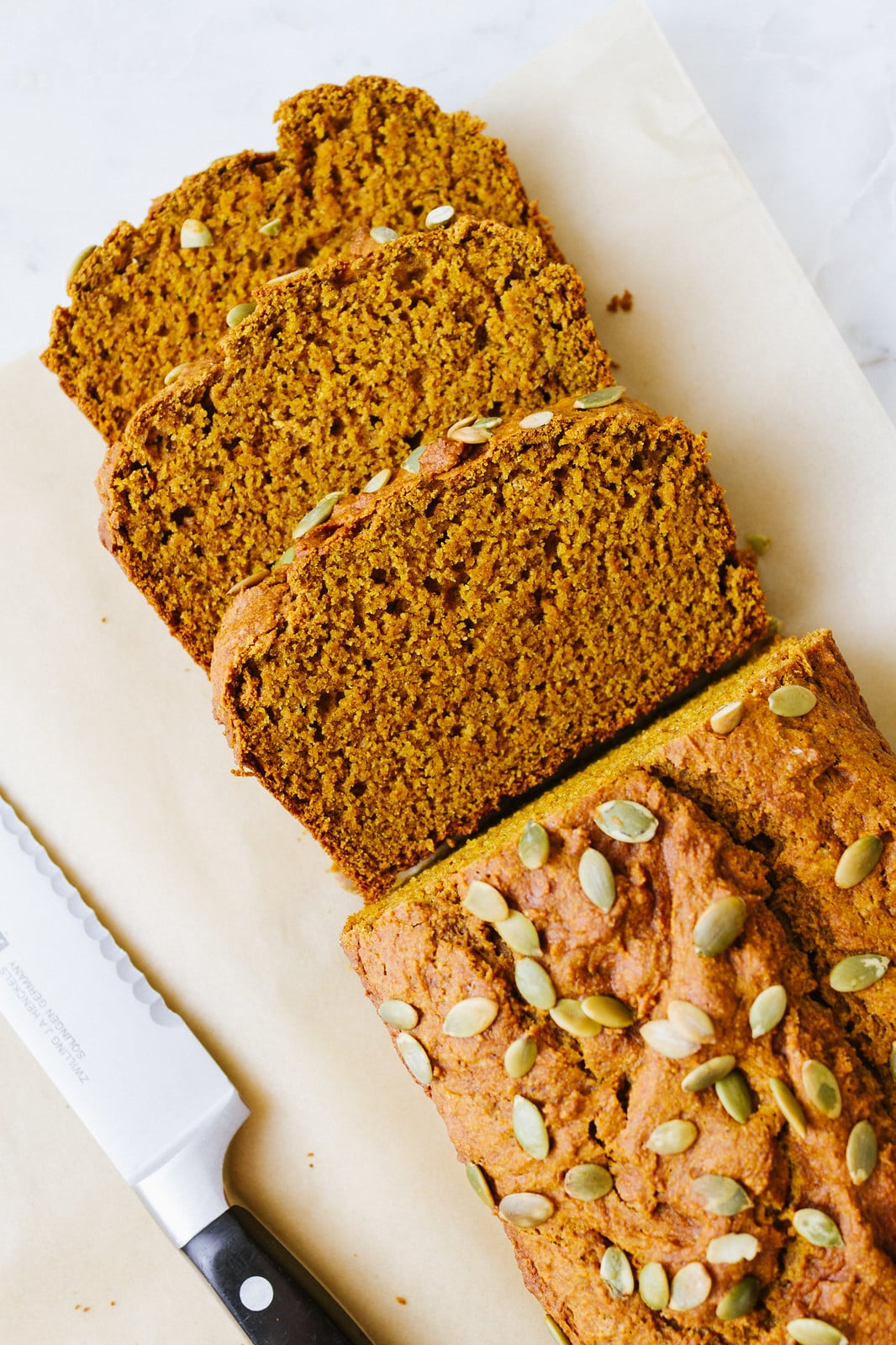 top down view of sliced vegan pumpkin bread on parchment paper.