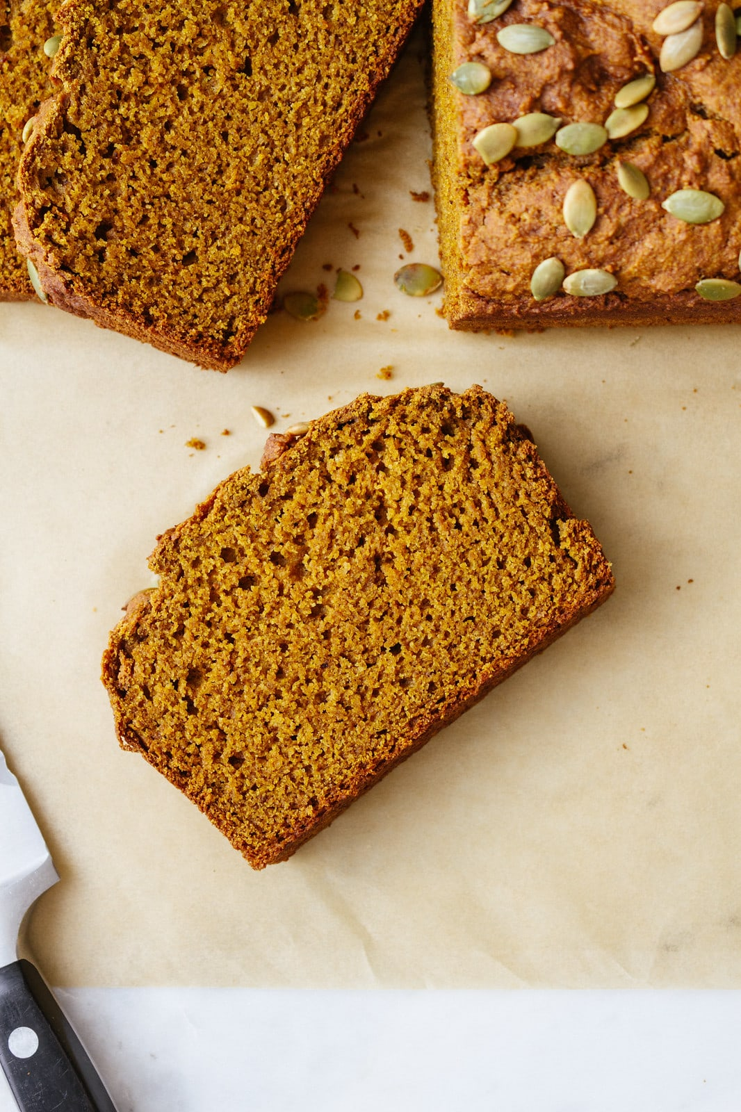 top down view of slice of vegan pumpkin bread on parchment paper with items surrounding.