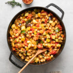 top down view of freshly made pot of chickpea ratatouille with items surrounding.