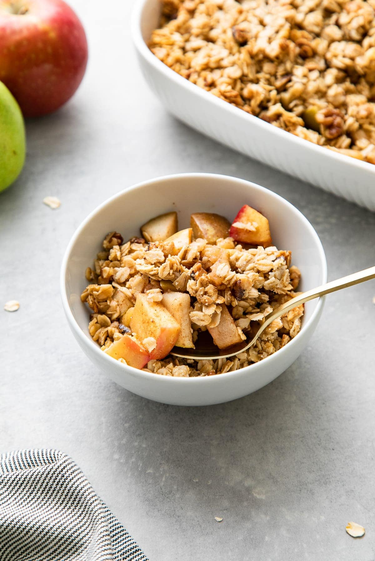 side angle view of vegan apple pear crisp in a white serving bowl with items surrounding.