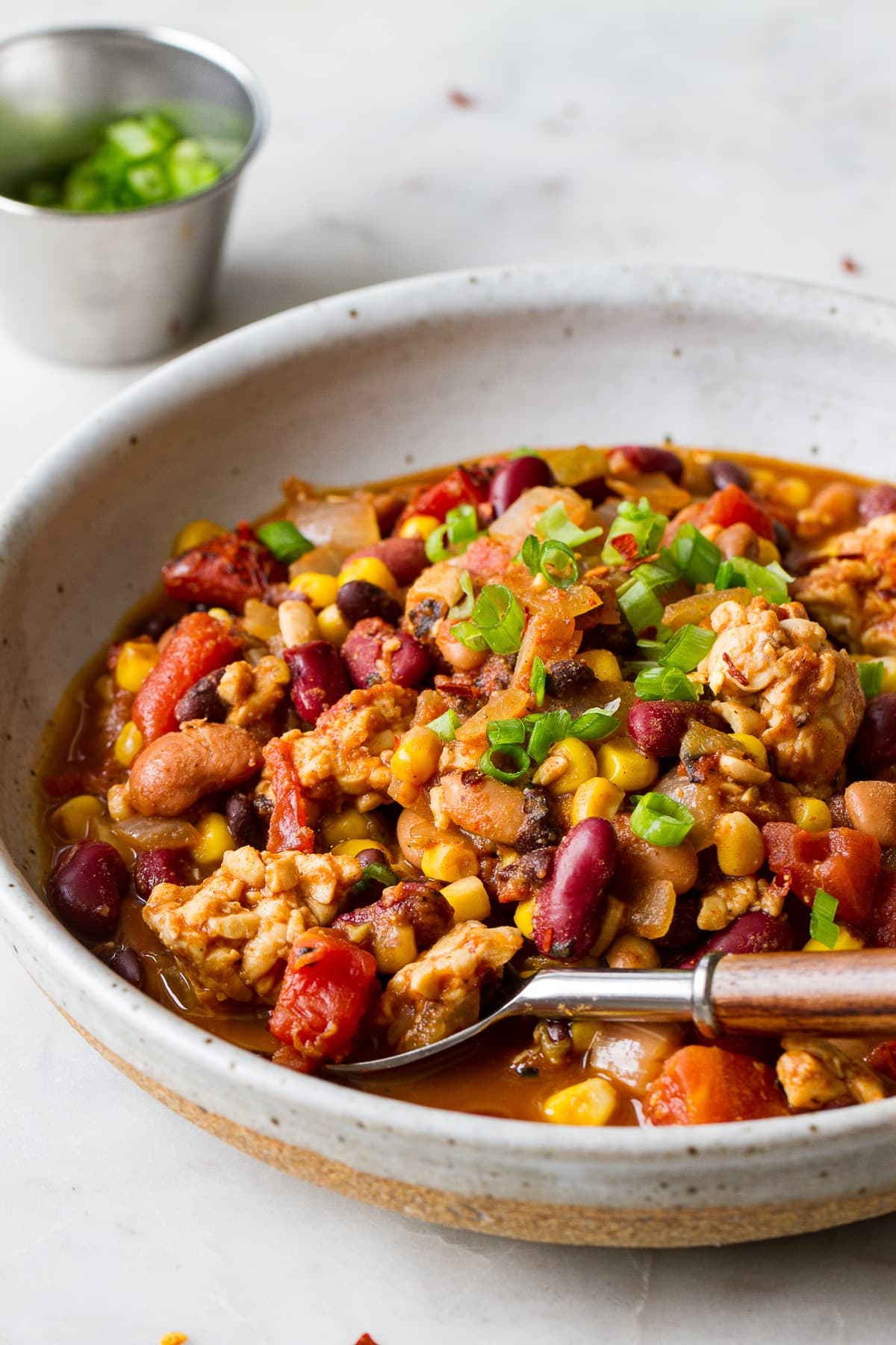 side angle view of a serving of vegan tempeh chili in a bowl with spoon.
