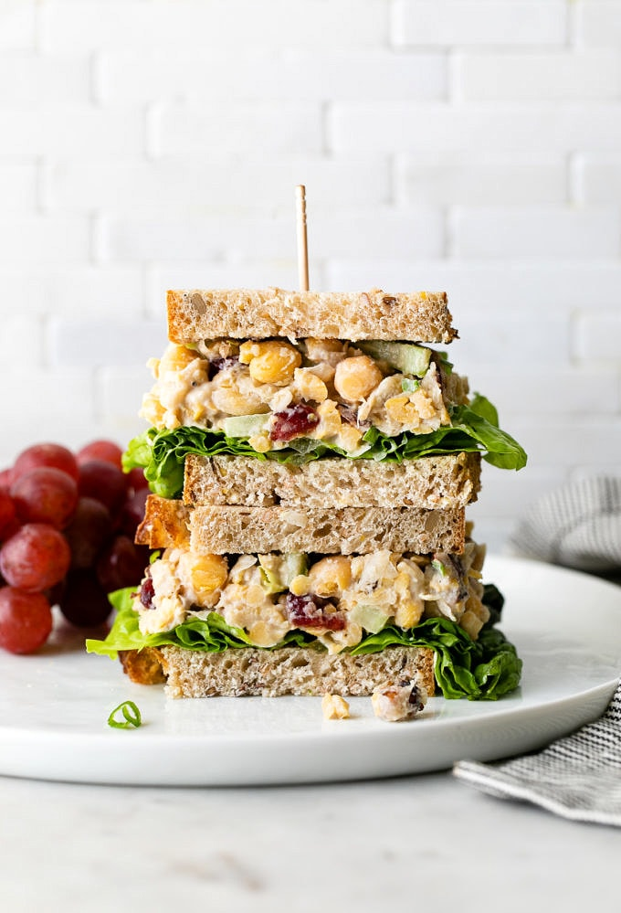 head on view of vegan chicken salad sandwich cut in half and stacked.