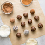 top down view showing the process of rolling energy balls in cocoa, cinnamon and coconut.