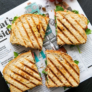 top down view of two grilled hummus sandwich sliced in half on newspaper.