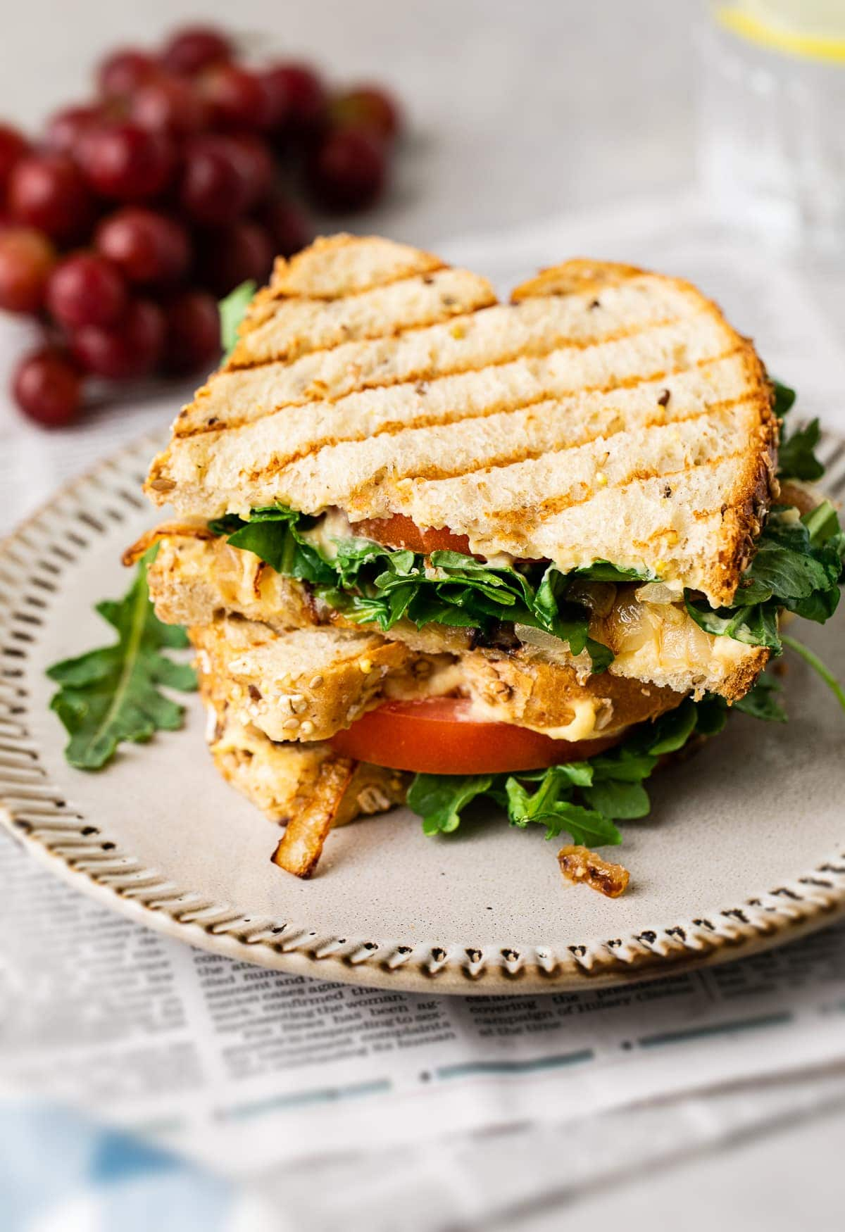 side angle view of two halves of grilled hummus sandwich stacked on a small plate.