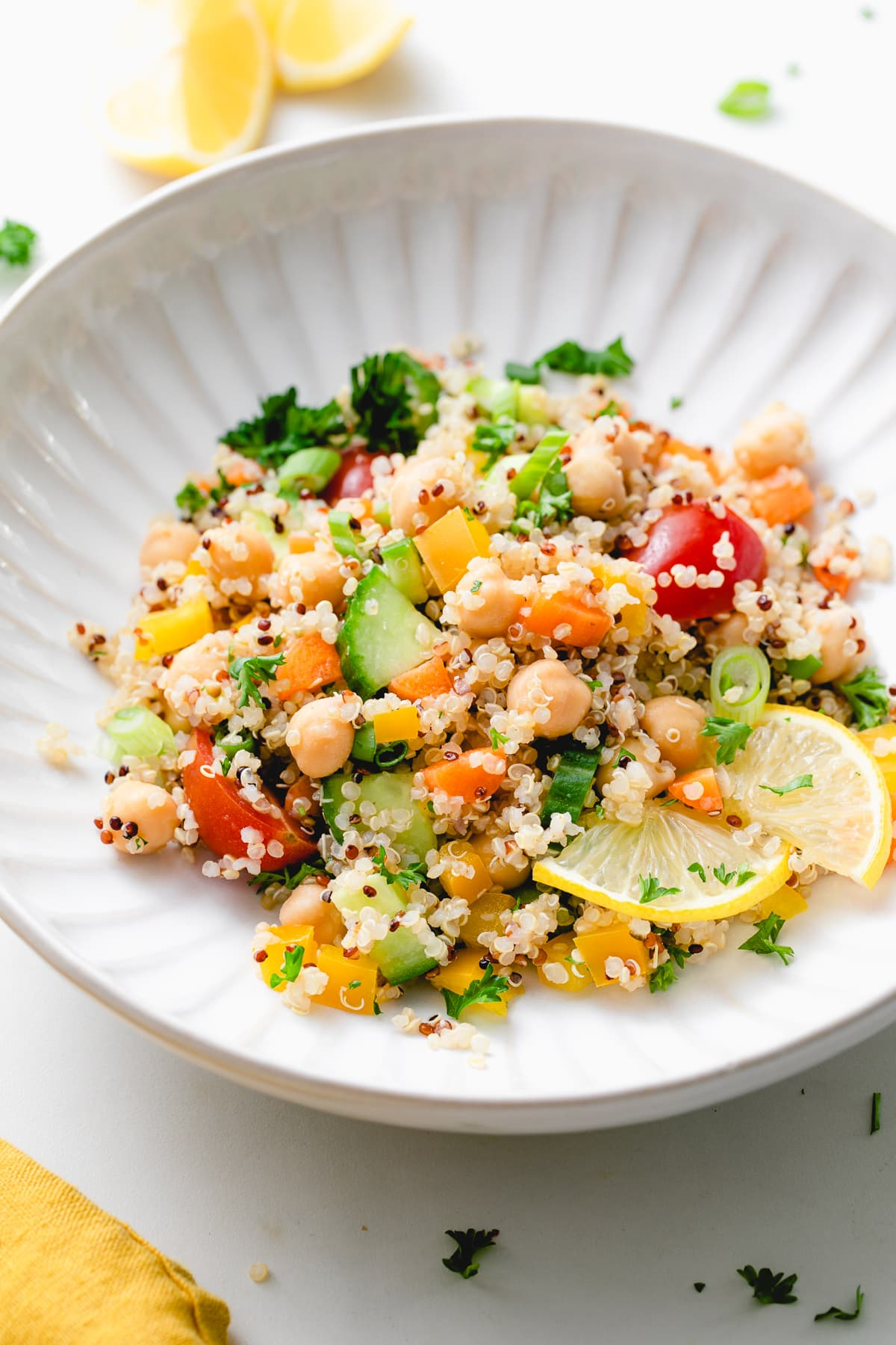 side angle view of lemon quinoa chickpea salad in a white bowl.