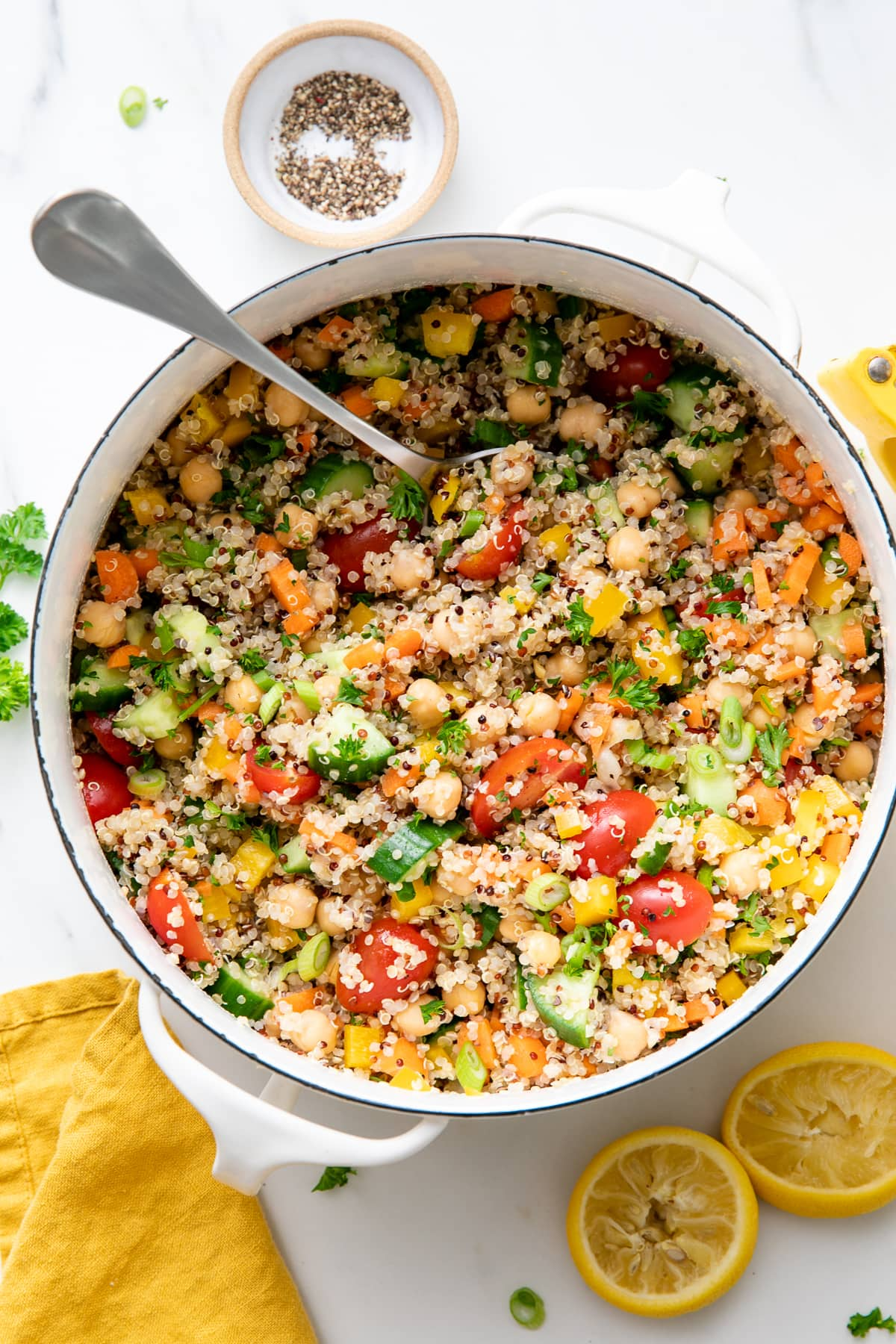 top down view of pot of freshly made healthy lemon quinoa chickpea salad with items surrounding.