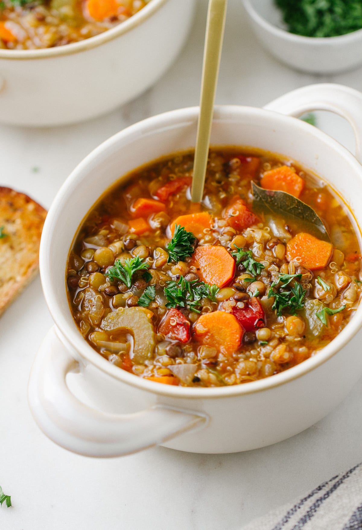side angle view of a bowl with a serving of healthy smoky lentil and quinoa soup with spoon.