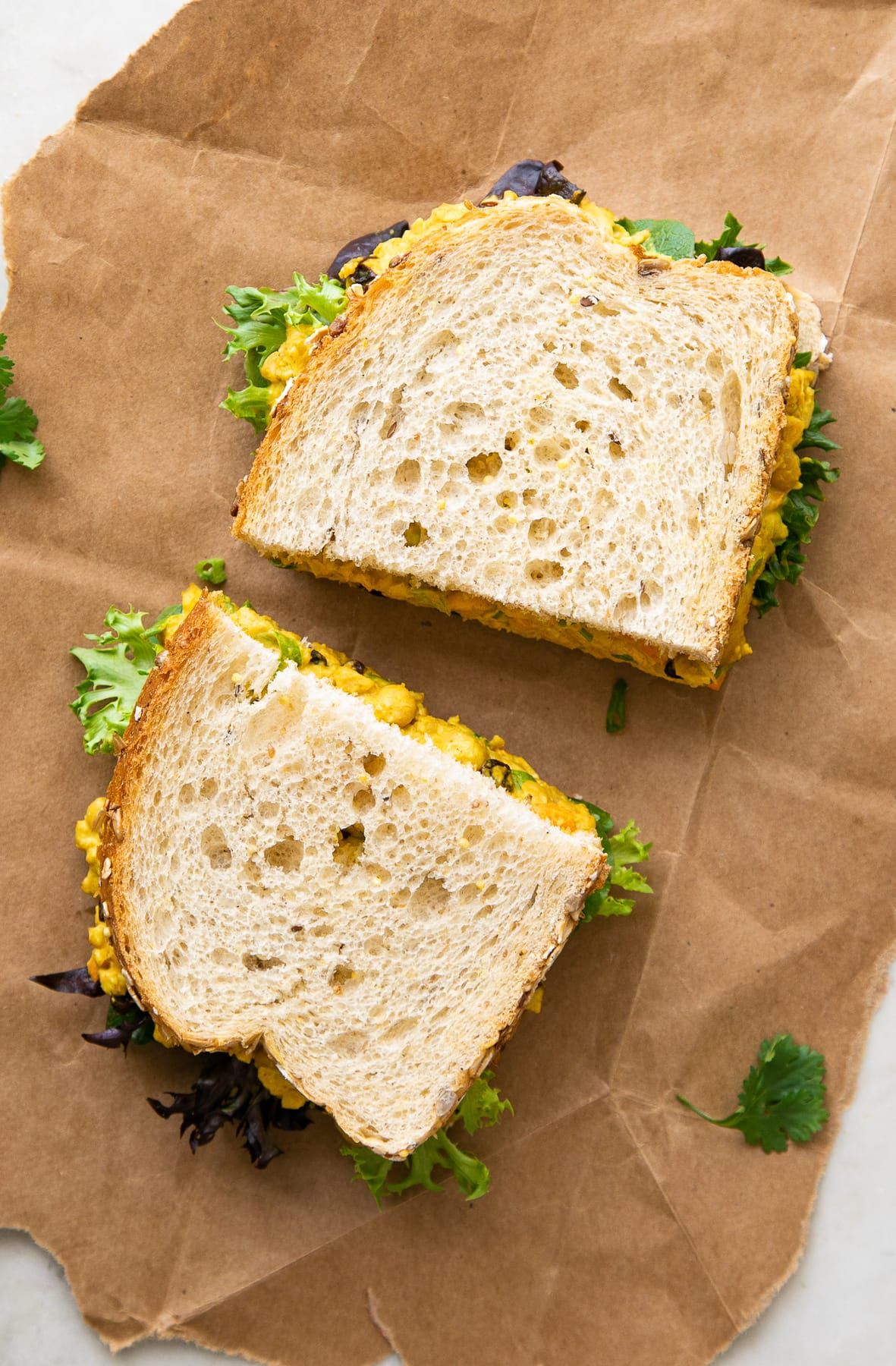 top down view of curried chickpea salad sandwich sliced in half on flat surface.