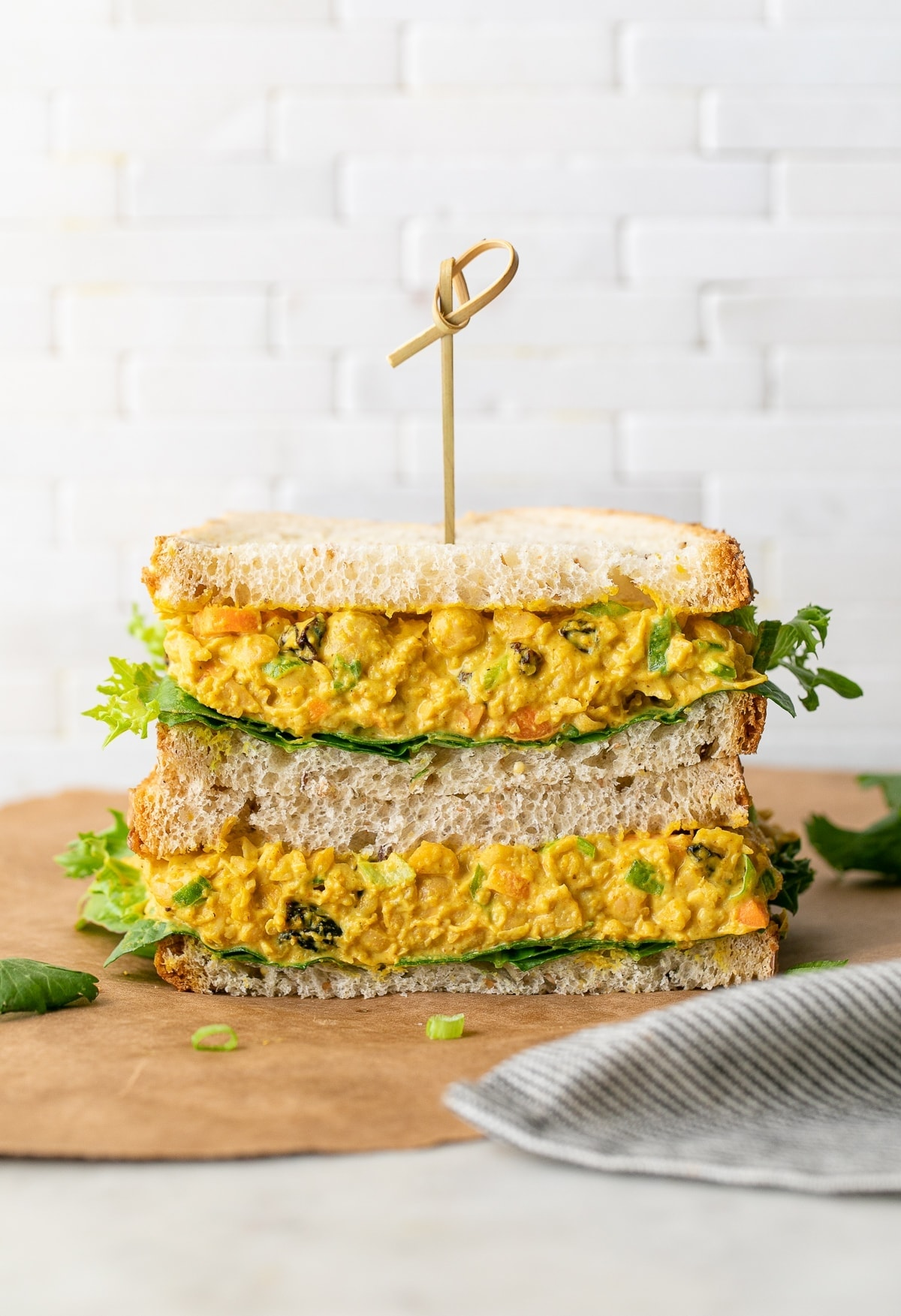 head on view of curried chickpea salad sandwich sliced in half and stacked.