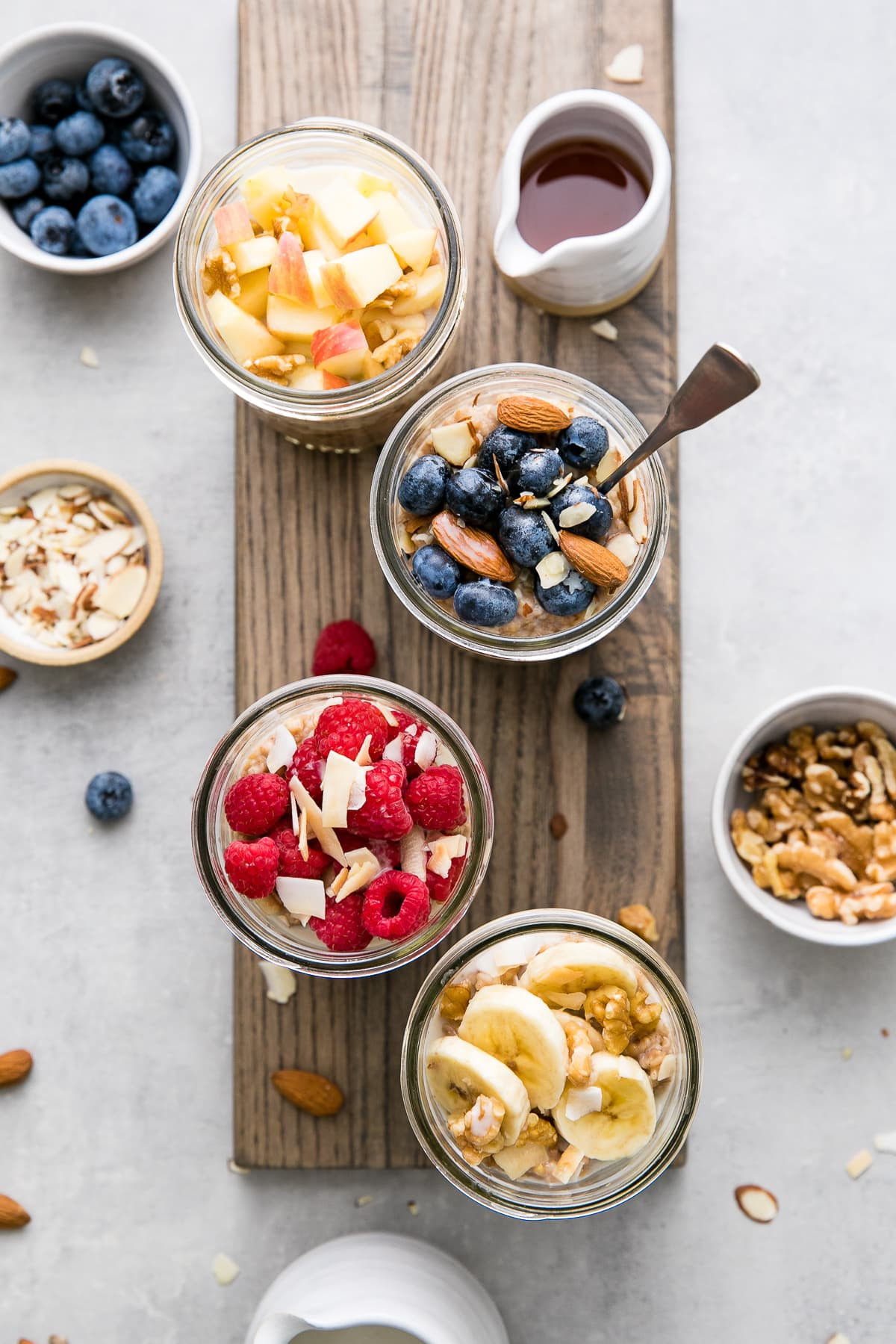 top down view of glass jars with steel cut oats and various fruits and nuts.