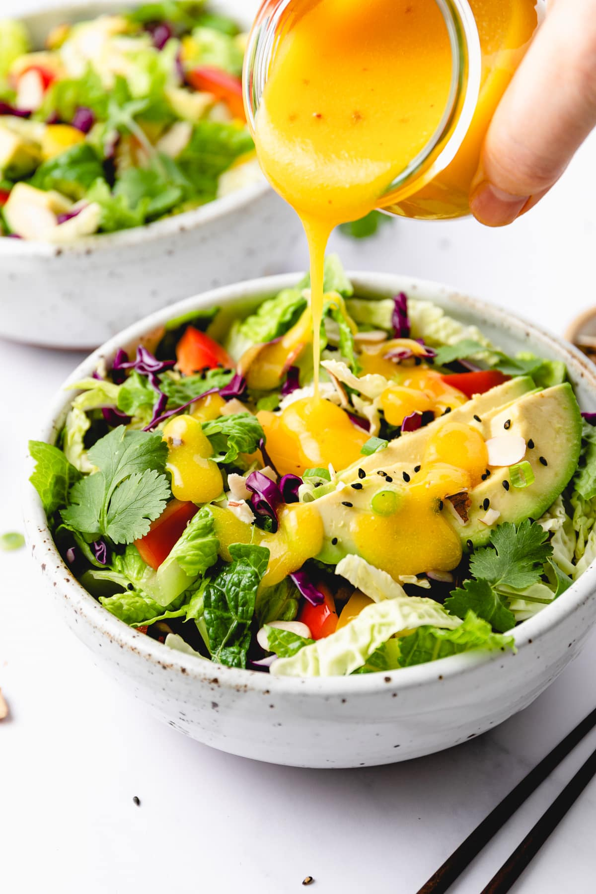 side angle view of mango dressing being poured over rainbow chop chop salad.