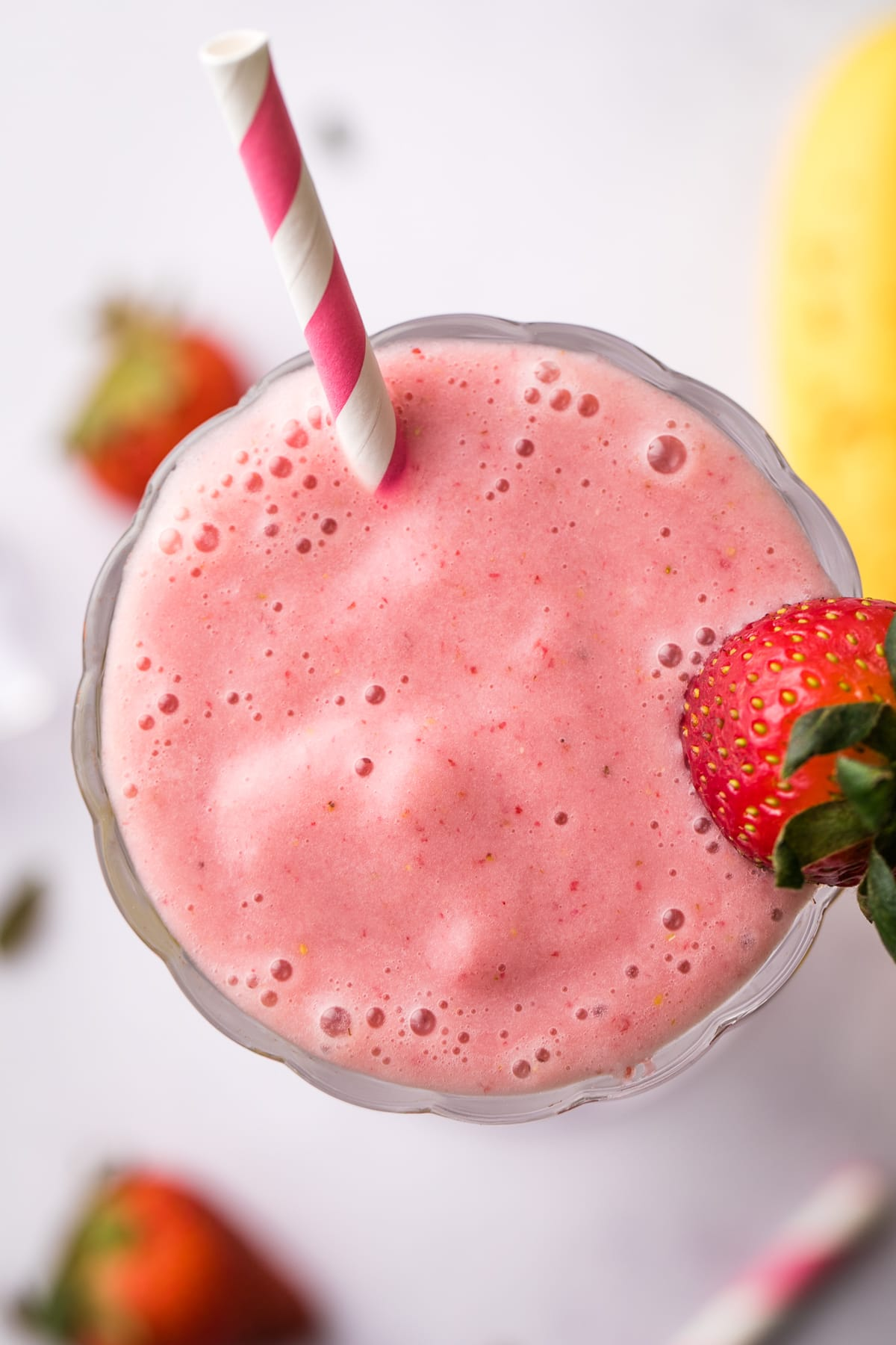 top down view of healthy vegan strawberry milkshake in a glass with items surrounding.