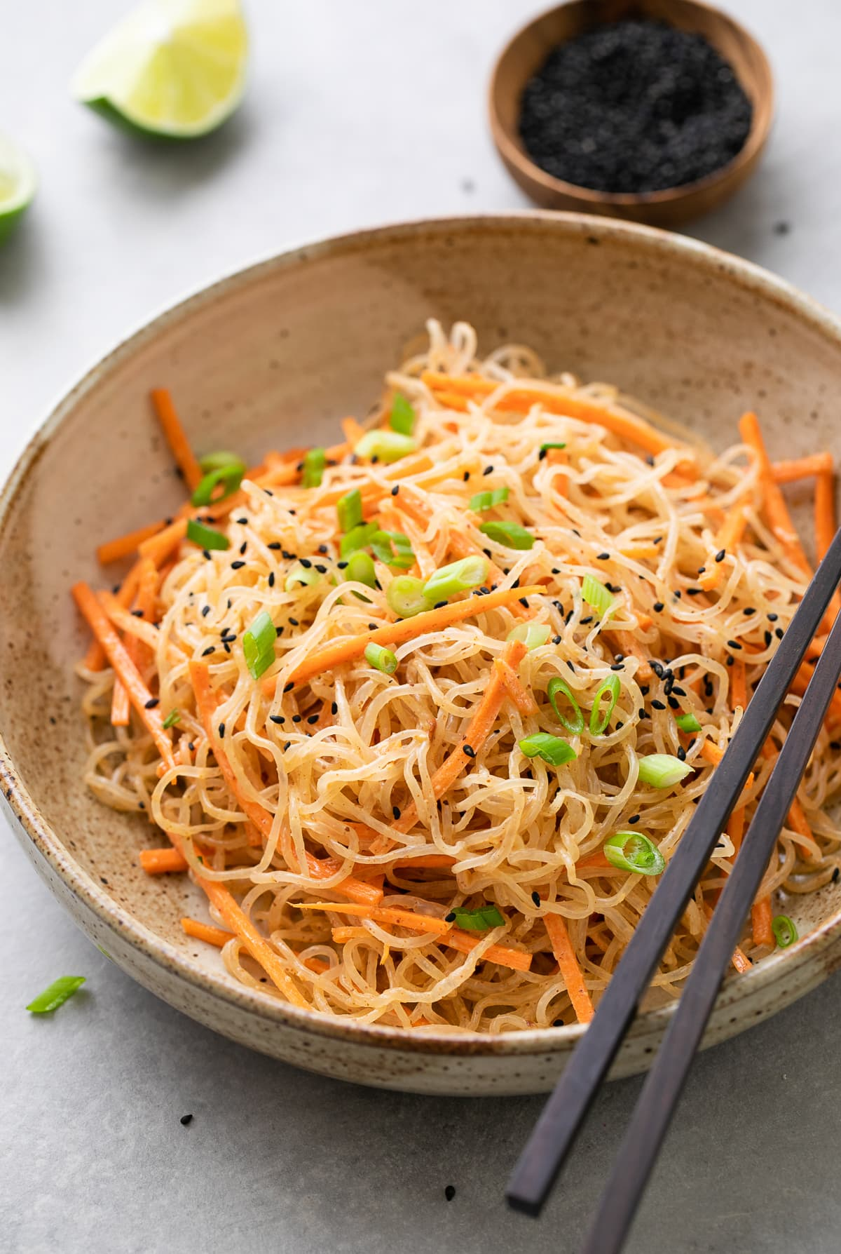 side angle view of serving of kelp noodle salad in bowl with chopsticks and items surrounding.