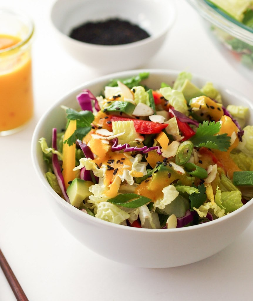 rainbow salad with mango dressing in a white bowl and ready to eat