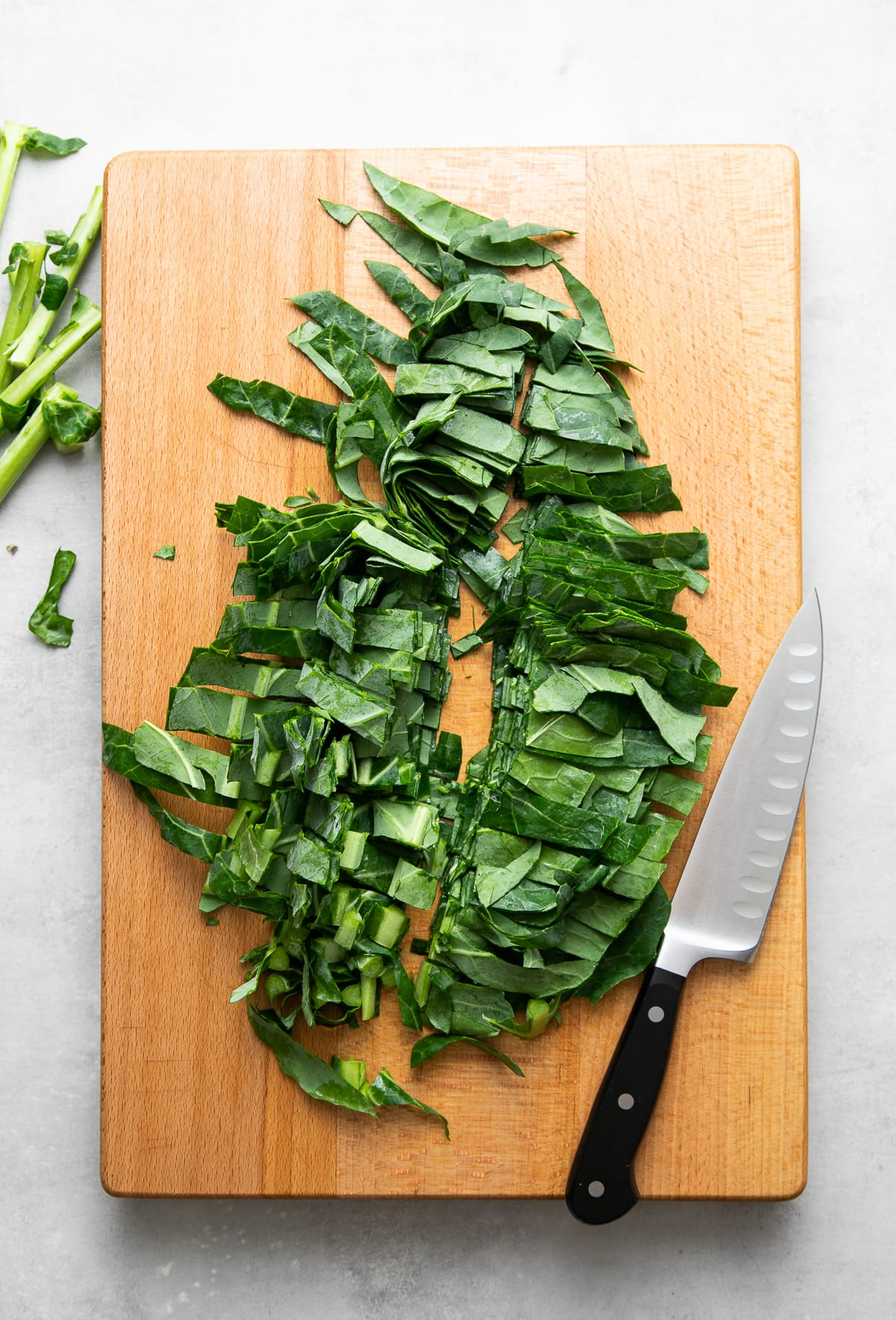 top down view of chopped collard greens on a wooden cutting board.