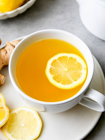 top down view of lemon ginger detox tea in a cup with lemon and items surrounding.