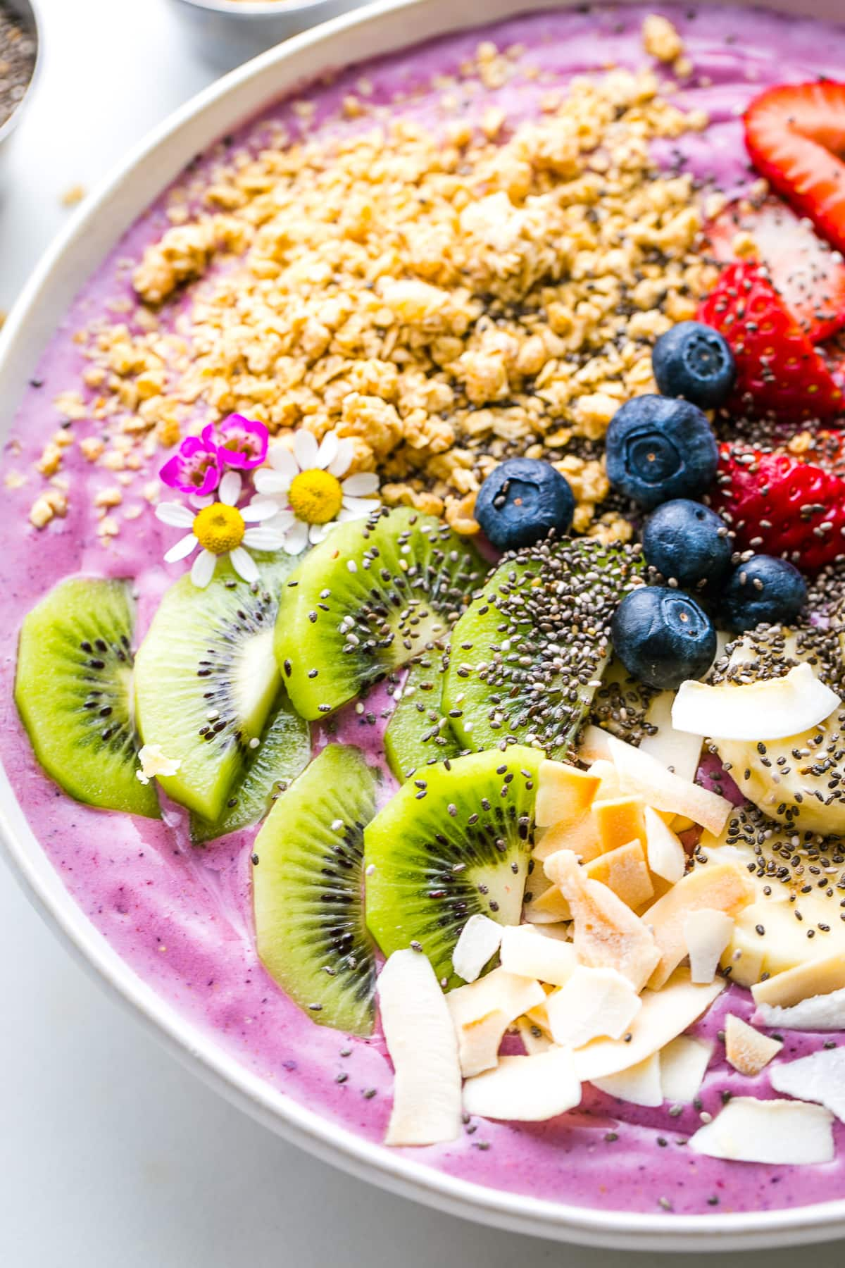 side angle view of healthy smoothie bowl with variety of toppings and items surrounding.