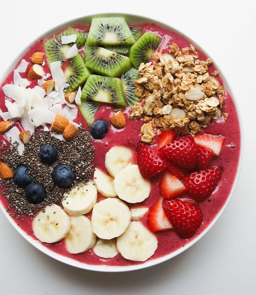 top down view of smoothie bowl topped with sliced fruits, nuts, seeds and granola and coconut.