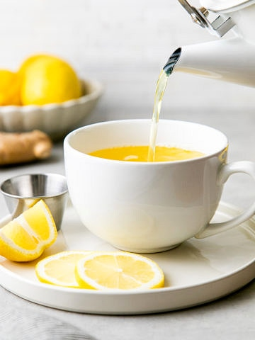 head on view of kettle pouring lemon ginger detox tea with items surrounding.