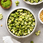 top down view of serving bowl with green matcha stovetop popcorn with items surrounding.