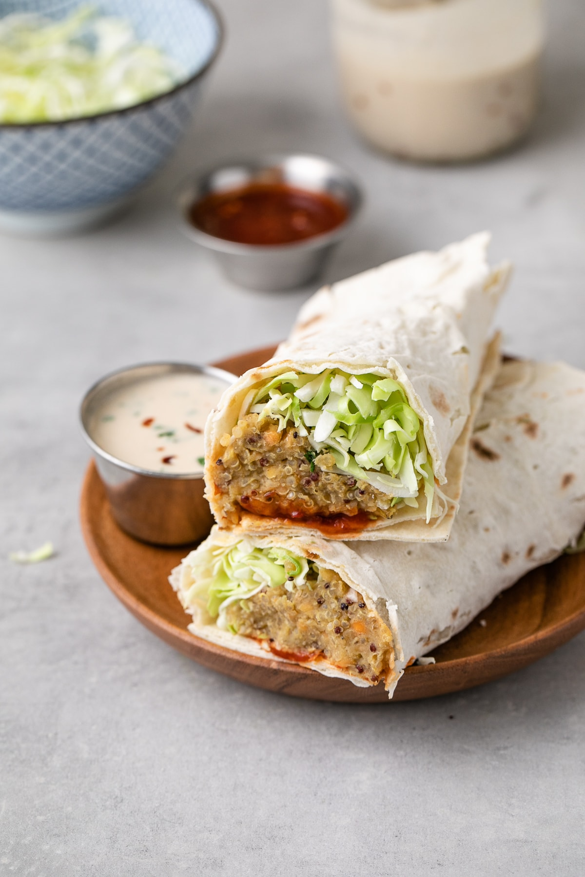 side angle view of spicy quinoa lentil wraps cut in half on a small wooden plate with items surrounding.